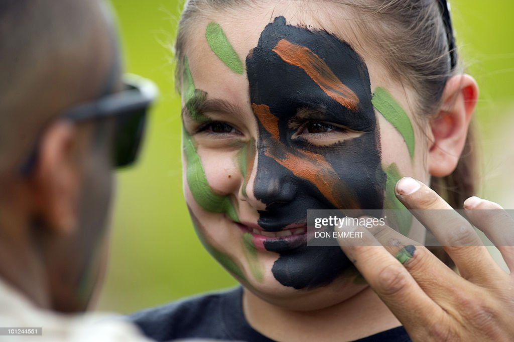Marine paints the face of a girl with camouflage as the US Marines conduct a public helicopter demonstration May 28, 2010 at Orchard Beach, Bronx, NY. The event was one of many held this week as New York City celebrates Fleet Week.