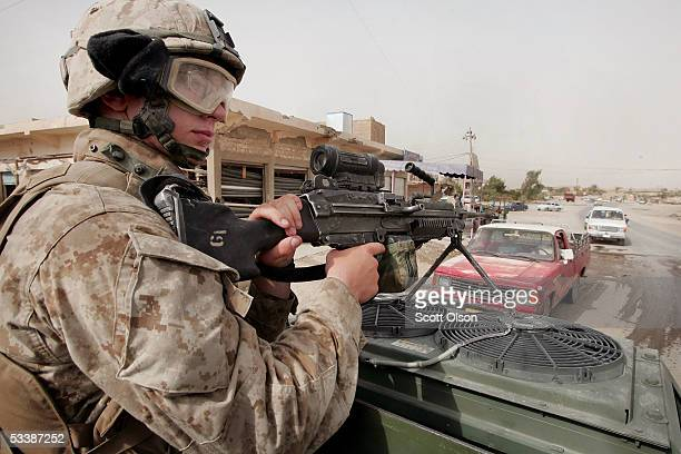 S Marine Pfc Jacob Williams stops traffic as a patrol of Marines from Golf Company 2nd Battalion 7th Marines patrols August 14 2005 in Fallujah Iraq...