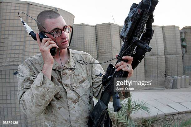 S Marine Pfc Ryan Atkins from Echo Company 2nd Battalion 7th Marines talks to his mother on a satelite phone August 12 2005 in Fallujah Iraq The...