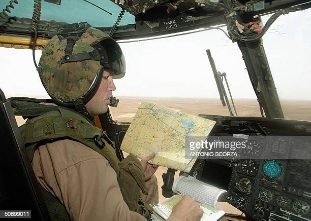 Marine pilot captain Denis Hahn reads a map while flying a C853 helicopter 26 May 2004 transporting supplies between alAsad air base and alQaim...