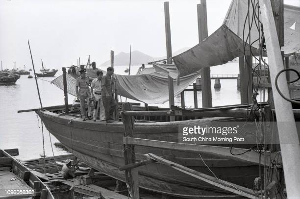 Marine Police officers inspecting a fishing boat which took Vietnamese refugees to Hong Kong in a twomonth voyage Refugees on the boat may have...