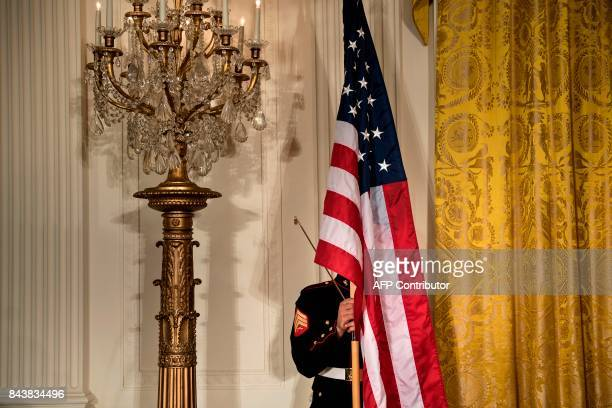 A Marine prepares an American flag for a press conference with Kuwait's Emir Sheikh Sabah alAhmad AlSabah and US President Donald Trump in the East...