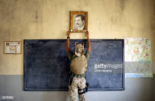 S Marine pulls down a picture of Saddam Hussein at a school April 16 2003 in AlKut Iraq A combination team of Marines Army and Special Forces went to...
