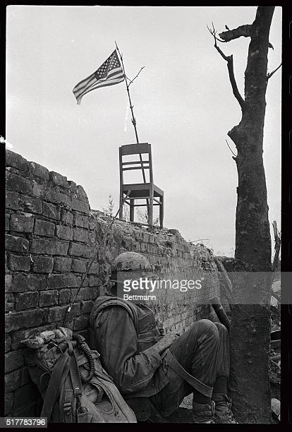 A Marine radioman takes a breather along the wall of the Citadel in Hue A makeshift flagpole and a chair support the American flag which flies over...