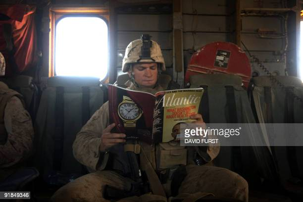 Marine reads a copy of Atlantic magazine with a cover photo of US President Barack Obama as he rides on a CH53 helicopter flying over Helmand...