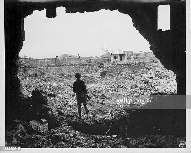 Marine Rifleman viewing the results of US bombardment of Naha, during the Pacific Campaign of World War Two, Okinawa, Japan, circa 1943-1945.