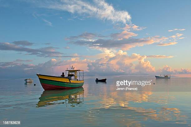 Marine scene with boats on a glassy sea at sunset