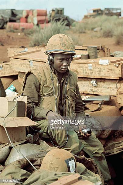 US Marine seated listening to his radio equipment during a lull in shelling