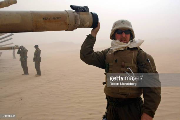 Marine Sergeant from the 1st Marine Division Tanks caps the barrel of a M1A1 Abrams tank during a 45 mph sandstorm February 3 while waiting for...