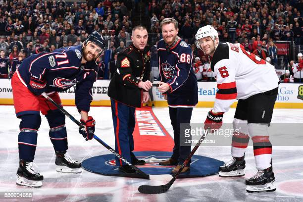 Marine Sergeant Sean Landis and Dale Earnhardt Jr drop the ceremonial first puck for Nick Foligno of the Columbus Blue Jackets and Andy Greene of the...