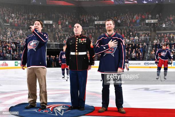 Marine Sergeant Sean Landis and Dale Earnhardt Jr stand as Leo Welsh sings the national anthem prior to a game between the Columbus Blue Jackets and...