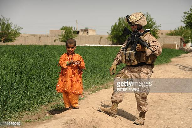 US Marine Sgt Jessica Clymen from Regimental Combat Team 8 talks to a young Afghan girl in the town of Musa Qala in Helmand province on April 9 2011...