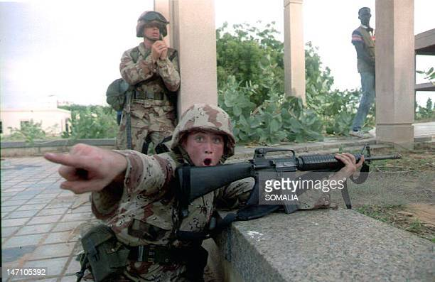 Marine shouts orders to reporters and photographers to keep out of the premises as he advances with his comrades toward the destroyed building of the...