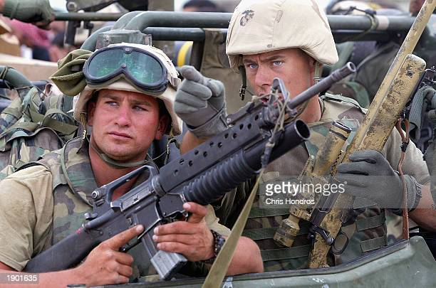 QAL'AT SUKKAR IRAQ APRIL 7 A US Marine sniper siganls to his colleague April 7 2003 in Qal'at Sukkar Iraq The 24th Marine Expeditionary Unit entered...