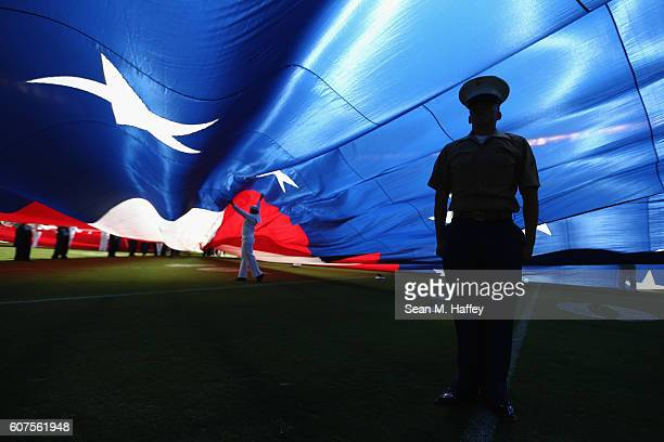 S Marine stands at attention under a large American flag before a game between the Jacksonville Jaguars and the San Diego Chargers at Qualcomm...