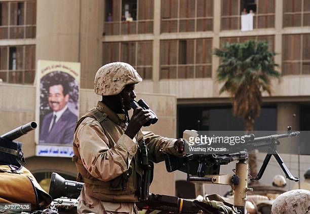 A US marine stands guard as a picture of Iraqi dictator Saddam Hussein is seen on April 9 2003 in Baghdad Iraq The third year anniversary since the...
