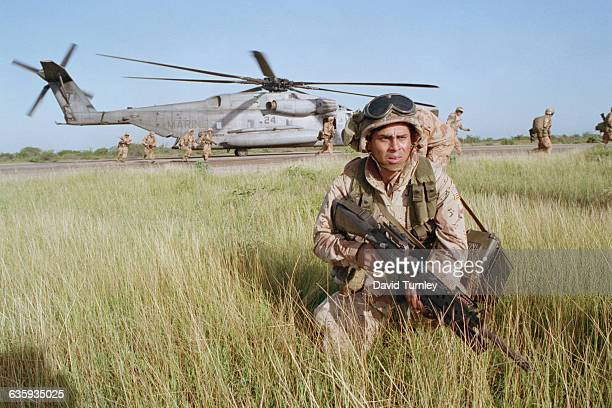 Marine stays alert as a helicopter lands in Mogadishu during Operation Restore Hope.