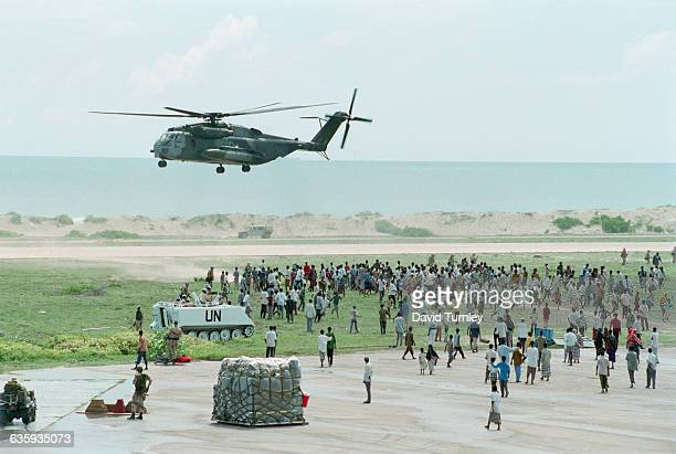 Marine Super Stallion transport helicopter prepares to land at a secured airbase amid a crowd of Somali civilians. This is the beginning of a US-led...