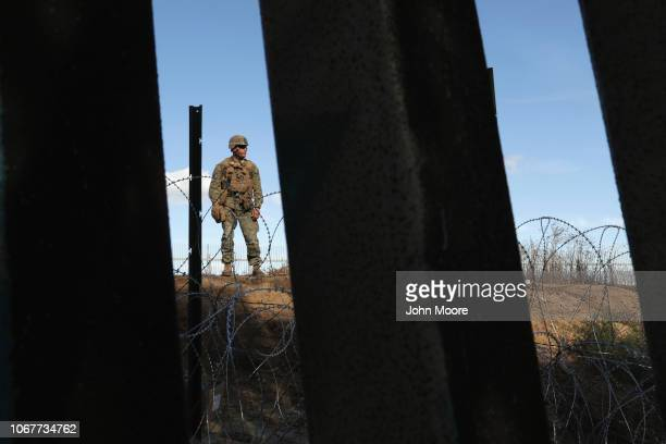 Marine supervises as fellow Marines install razor wire next to the U.S.-Mexico border fence on December 2, 2018 as seen from Tijuana, Mexico. Marines...
