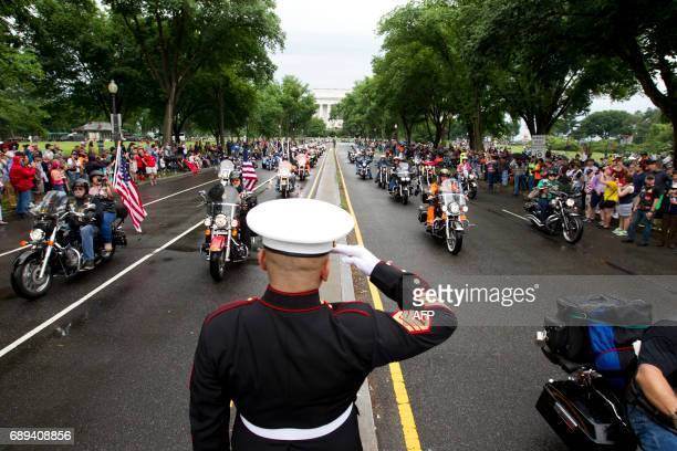 Marine Tim Chambers salutes as participants in the Rolling Thunder annual motorcycle rally ride in Washington DC on May 28 2017 Motorcyclists are in...
