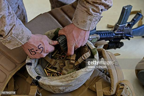 Marine unloads ammunition from a rifle magazine into his helmet after arriving in Kandahar on October 27 as British and US forces withdraw from the...