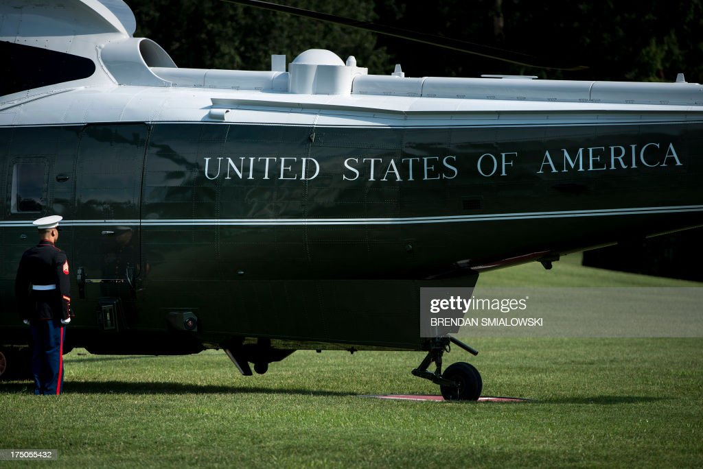 A Marine waits to open a door on Marine One after returning with US President Barack Obama on the South Lawn of the White House on July 30, 2013 in Washington. Obama was returning from a day trip to Tennessee where he toured an Amazon Fulfillment Center. AFP PHOTO/Brendan SMIALOWSKI