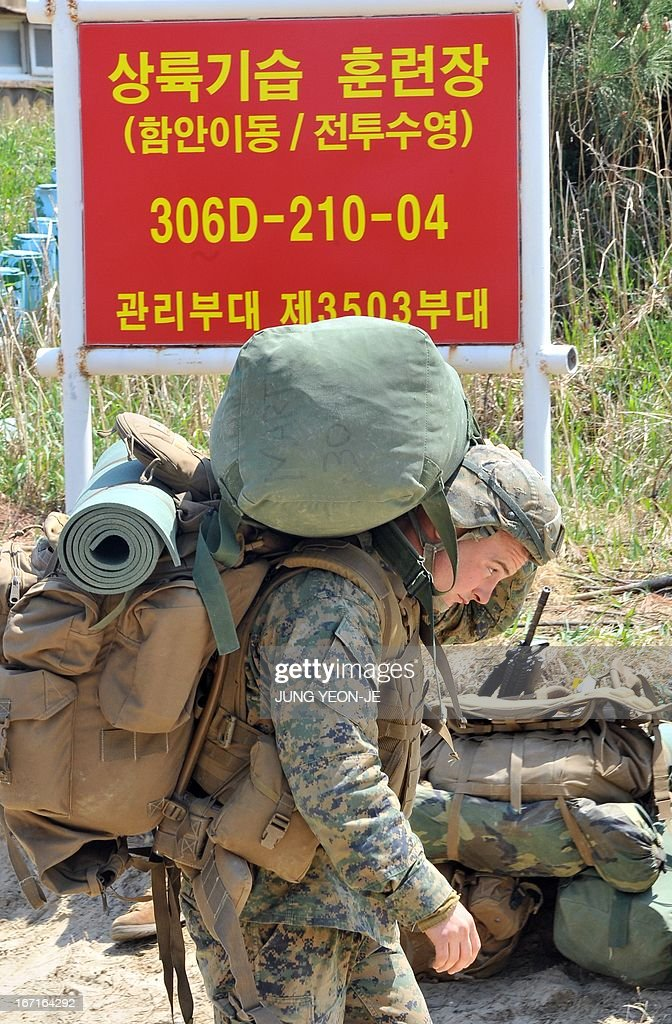 Marine walks past a red board reading 'landing training area' at a beach during the Combined Joint Logistics Over the Shore (CJLOTS) exercise in Pohang, 260 kms southeast of Seoul, on April 22, 2013. The wait for North Korea's expected missile test, which has kept South Korean and US forces on heightened alert for the past two weeks, may stretch to July, the South's defence ministry said on April 22.