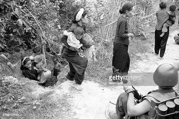A US Marine watches Vietnamese women and children come out from hiding in an intricate network of bunkers and trenches set up at the village of Lap...
