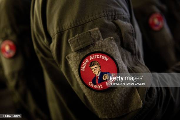 Marine wearing a badge listens to US President Donald Trump during a Memorial Day event aboard the amphibious assault ship USS Wasp in Yokosuka on...