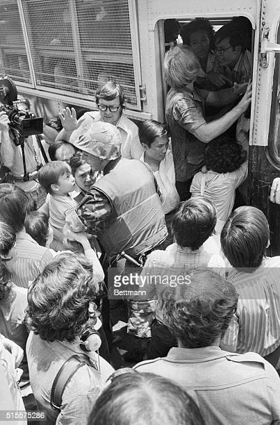 US Marine wearing helmet and flakjacket pushes away Vietnamese civilians trying to board bus leaving for an evacuation site April 29th American...