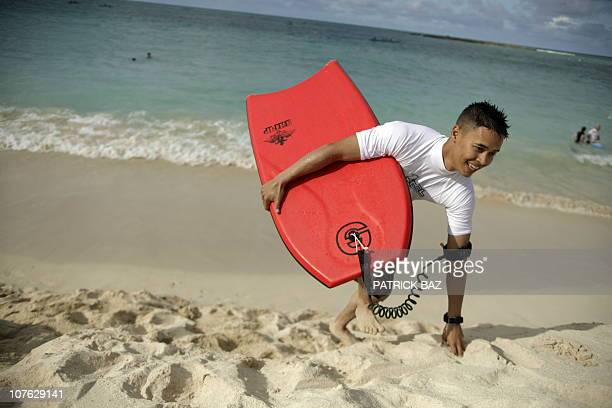 US marine with 1/3 marine Charlie company Cpl Matthew Delair from Hawaii hold his board as he runs on Kailua beach on the Hawaiian island of Oahu on...