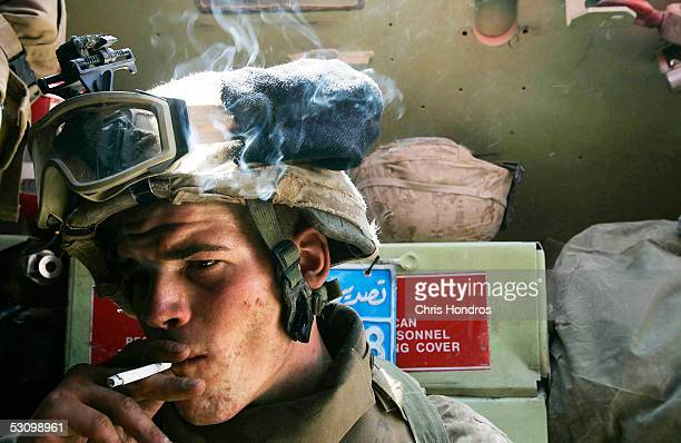 Marine with the 1st Battalion, Sixth Marines smokes a cigarette while in transit during Operation Dagger June 18, 2005 in Anbar Province, Iraq. The...