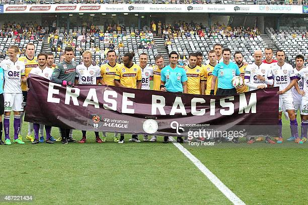 Mariners and Glory players hold a erase racism banner before the start of the match during the round 22 ALeague match between the Central Coast...