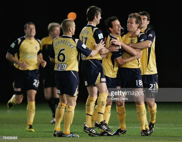 Mariners captain Alex Wilkinson celebrates with team mates after scoring the first goal during the round one A-League Pre-Season Cup match between...