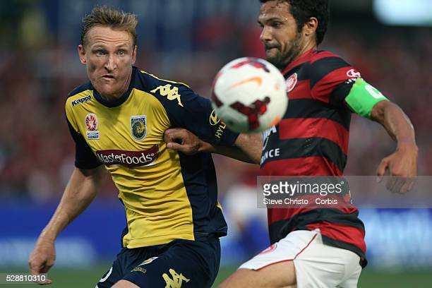 Mariners Daniel McBreen battles for the ball with Wanderers captain Nikola ToporStanley and ends up in the fence at Parramatta Stadium Sydney...