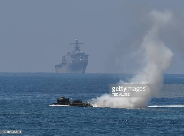 A US marines Amphibious Assault Vehicle speeds past USS Ashland during an amphibious landing exercise at the beach of the Philippine navy training...