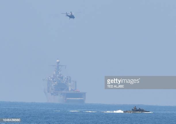 A US marines Amphibious Assault Vehicle speeds past USS Ashland while an attack helicopter hovers above during an amphibious landing exercise at the...