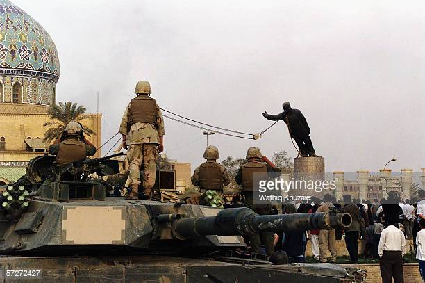 US marines and Iraqis are seen on April 9 2003 as the statue of Iraqi dictator Saddam Hussein is toppled at alFardous square in Baghdad Iraq The...