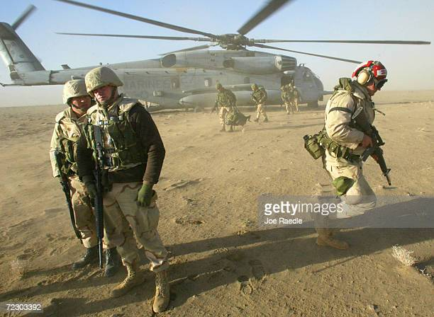 Marines and U.S. Army 10th Mountain Division soldiers depart from the Super Stallion helicopter to begin setting up the Forward Arming Refueling...
