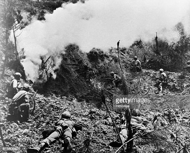 Marines await the results of an explosive charge set to kill any Japanese who attempt to escape from a cave in Okinawa. These caves formed the...