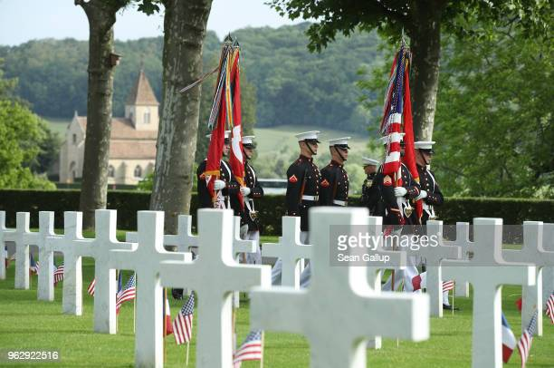 S Marines bear flags as they walk past the graves of US soldiers most of them killed in the World War I Battle of Belleau Wood before a ceremony to...