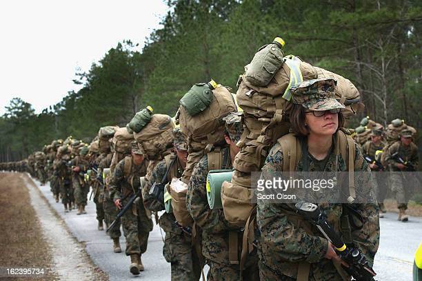 Marines, both male and female, participate in a 10 kilometer training march carrying 55 pound packs during Marine Combat Training on February 22,...