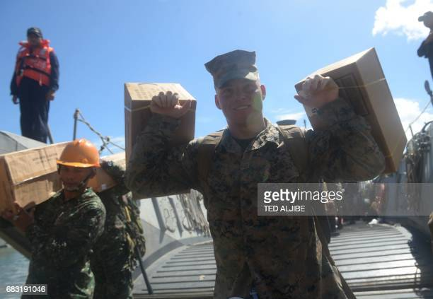 A US marines carries cargo as he disembarks from a Philippine landing ship during a simulation of a disaster drill as part of the annual joint...