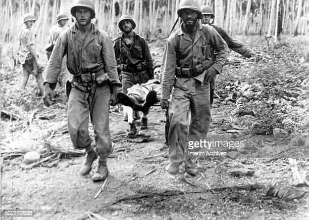 US Marines carry a wounded comrade on a stretcher during combat near the Kokumbona River Guadalcanal Solomon Islands 1942