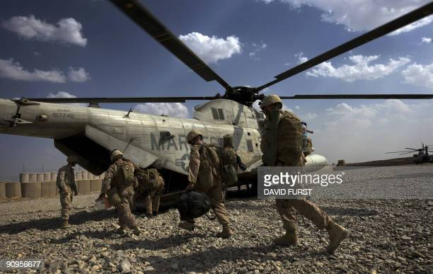 Marines carry their gear as they unload off a CH-53 helicopter at their base in Helmand Province, southern Afghanistan, on September 18, 2009....