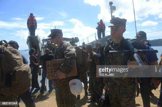 US marines carrying their cargo and communication equipment disembark from a Philippine landing ship during a simulation of a disaster drill as part...