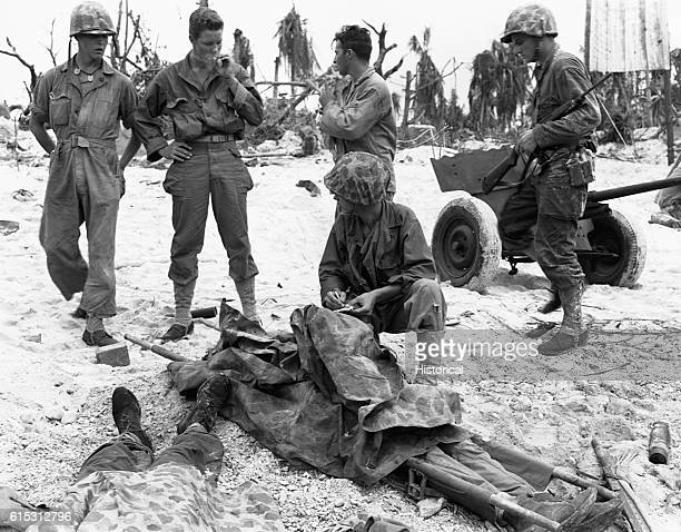 Marines check the bodies of comrades who were killed during the DDay attack on Peleliu