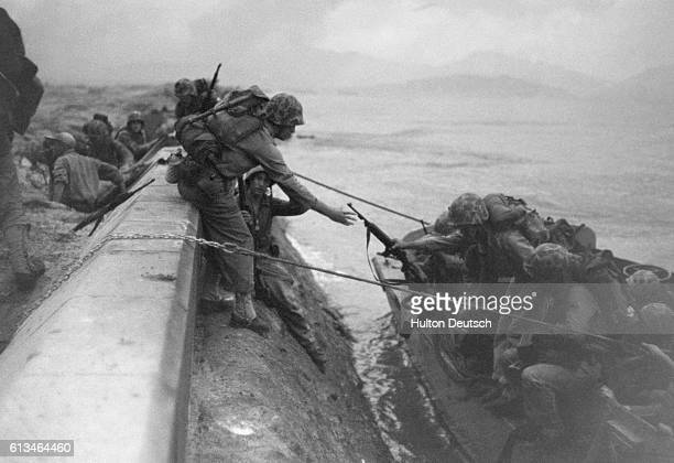 US Marines climb from their landing craft at the seawall in Inchon Korea