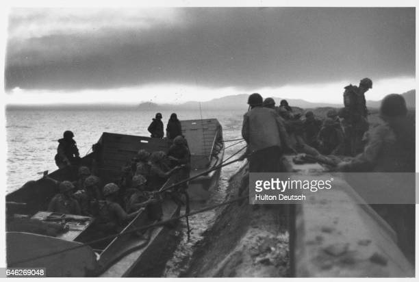 Marines climb from their landing craft at the seawall in Inchon, Korea.