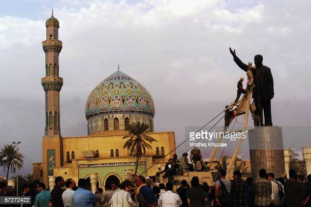 US marines climb up to topple a statue of Iraqi dictator Saddam Hussein on April 9 2003 at alFardous square in Baghdad Iraq The third year...